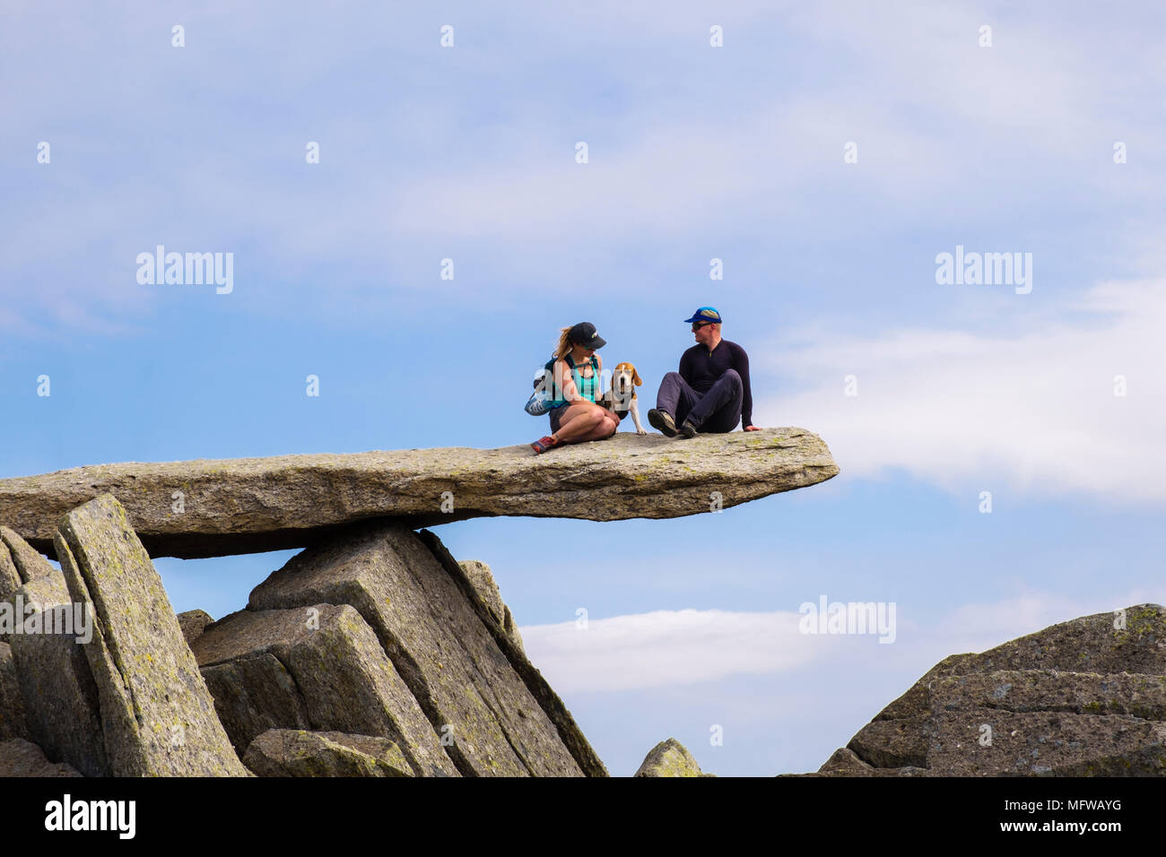 Hikers with a dog sat on the cantilever rock slab on Glyder Fach mountain in Snowdonia National Park. Wales, UK, Britain - Stock Image