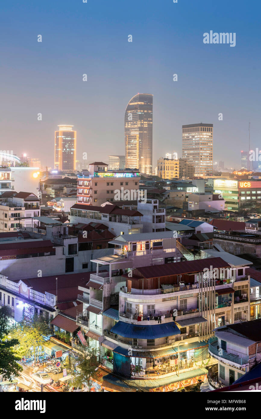 Skyline of Phnom Penh with illuminated buildings in the Central Business District and in foreground, the Central market and river bank tourist area - Stock Image