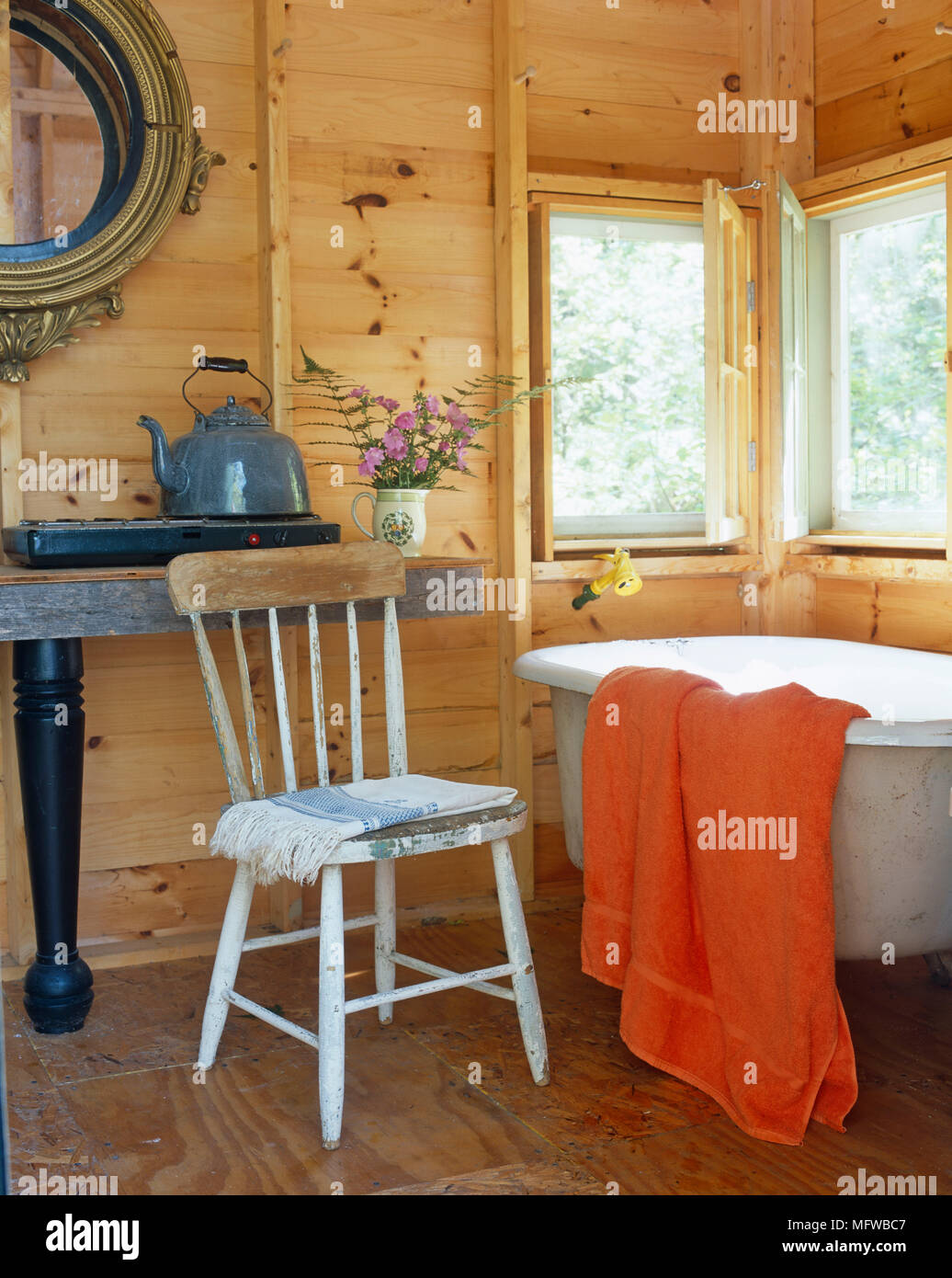 Rustic wooden chair next to old fashioned roll top bathtub Stock ...