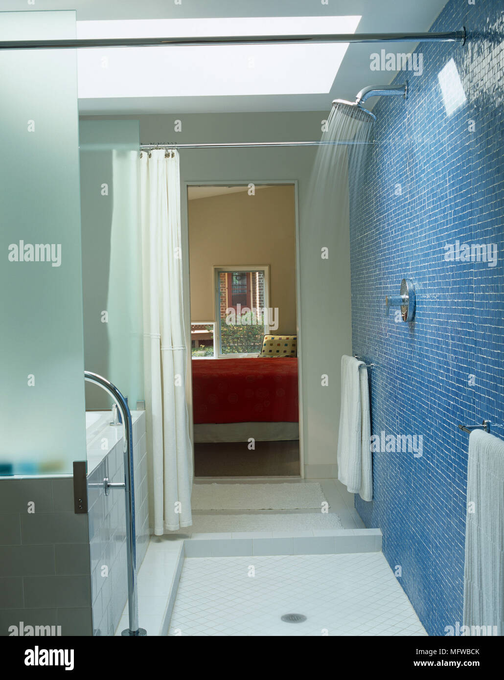 Shower with running water in blue tiled bathroom Stock Photo ...