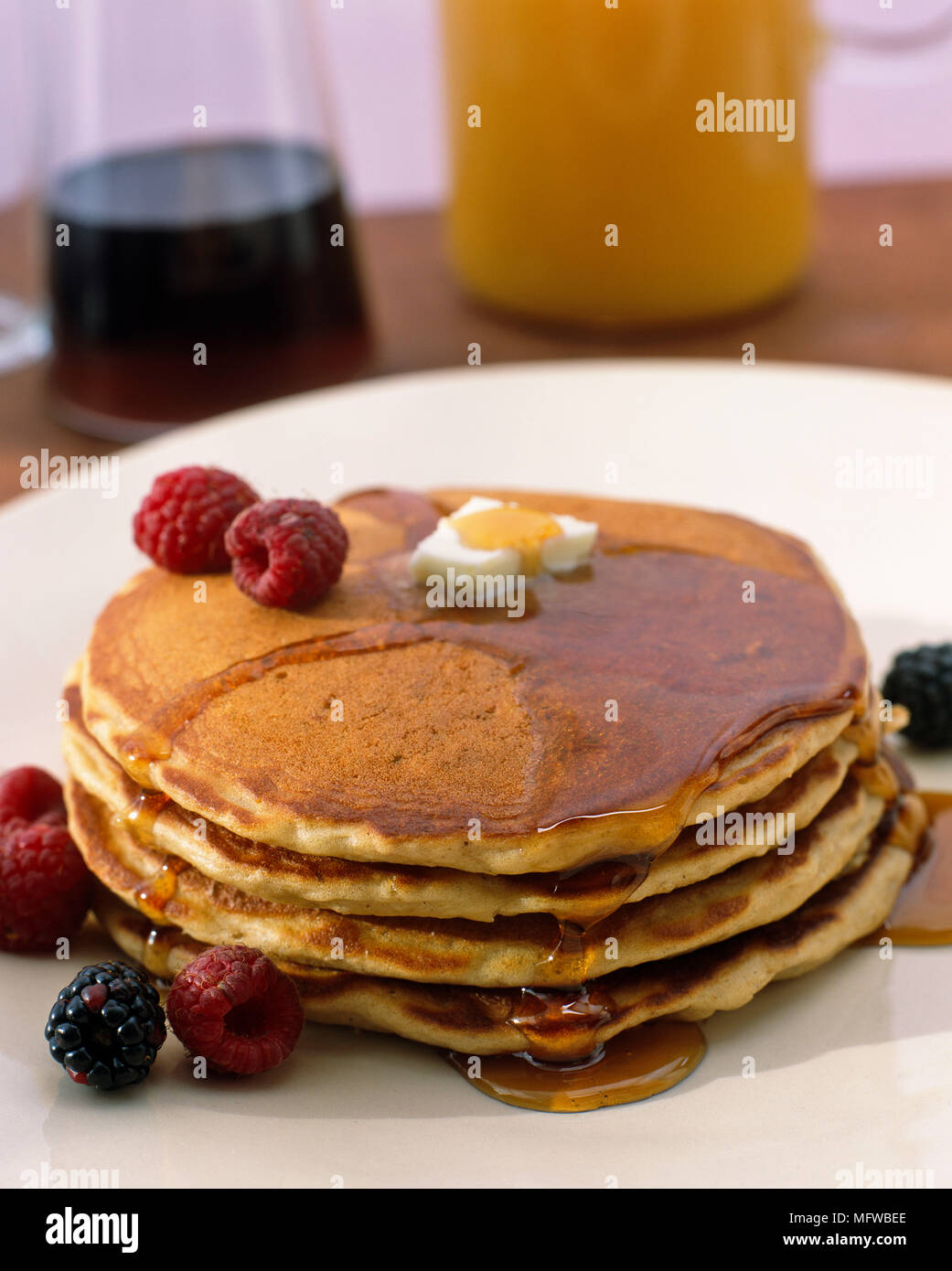 Stack of pancakes with maple syrup and fresh fruit - Stock Image
