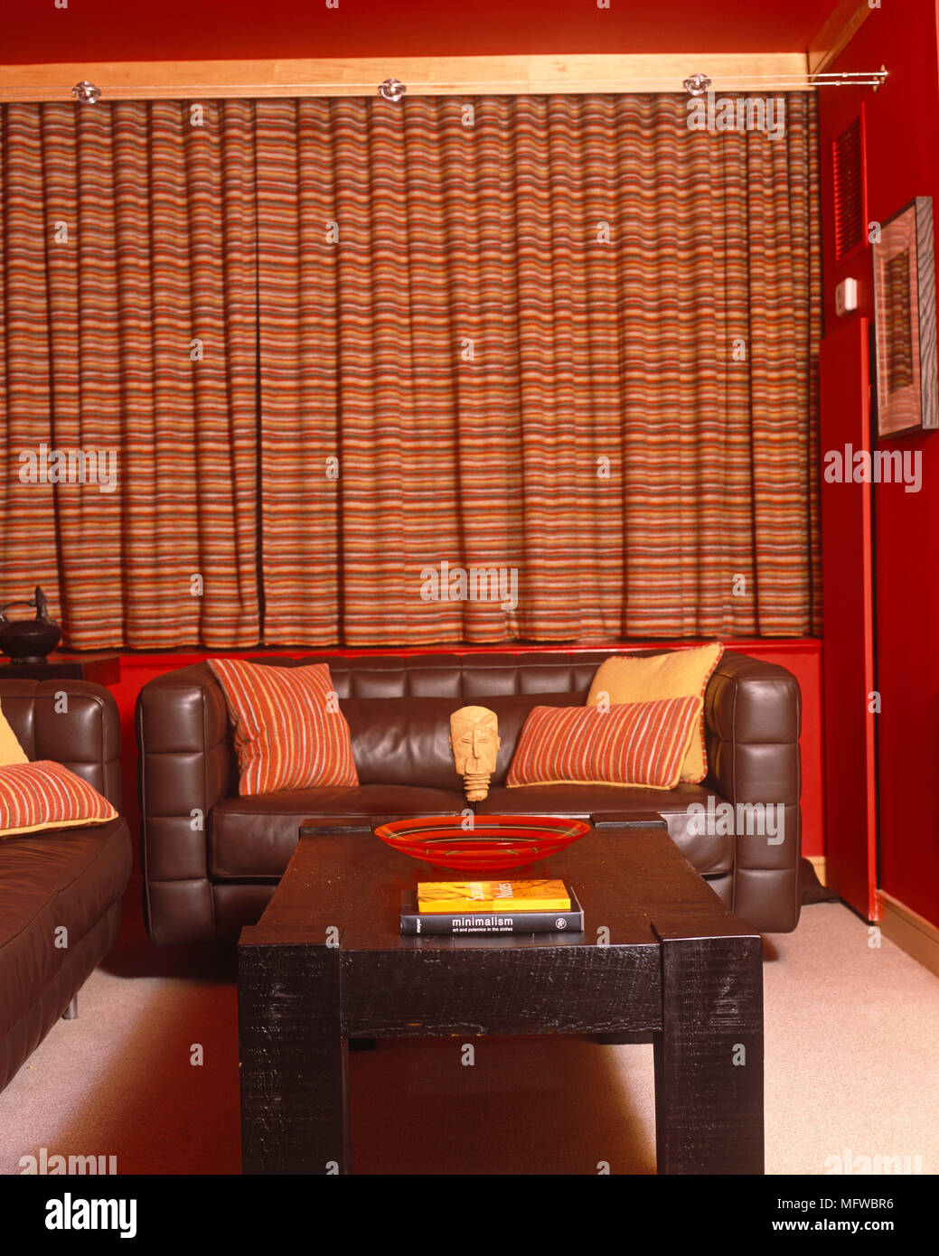 Upholstered leather sofa in front of window with red pattern ...