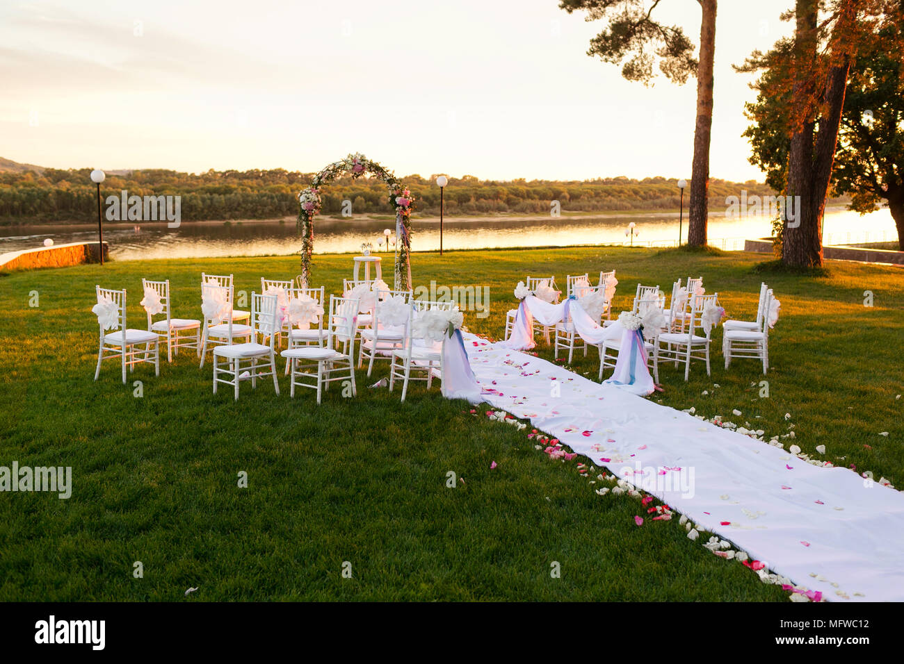 sunset on river romantic wedding ceremony white wooden chairs with