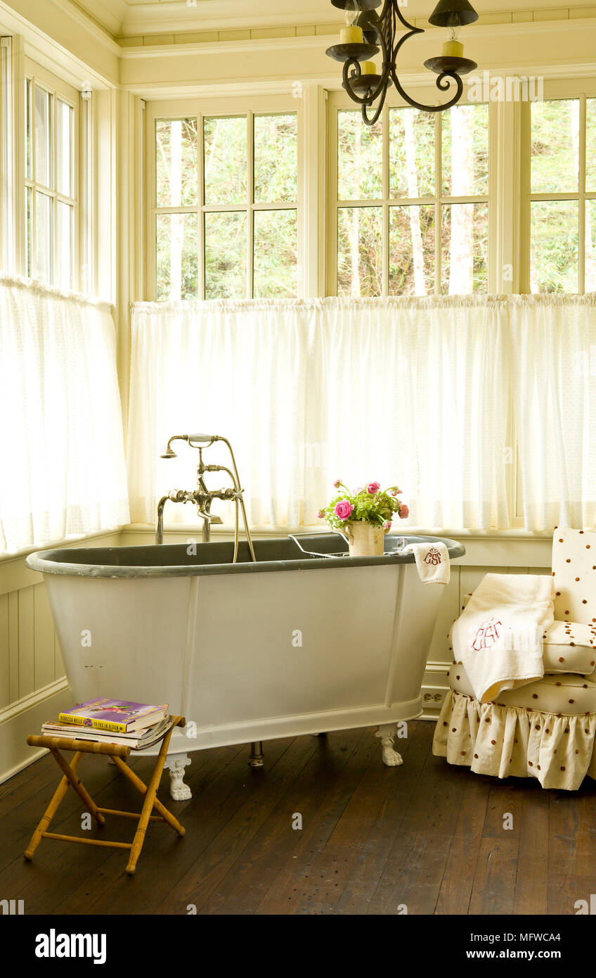 Old fashioned style freestanding bathtub in corner of country style ...