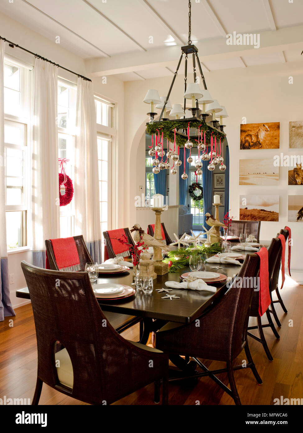 christmas decorations hanging from chandelier above table laid for lunch in country style dining room - Christmas Chandelier Decorations
