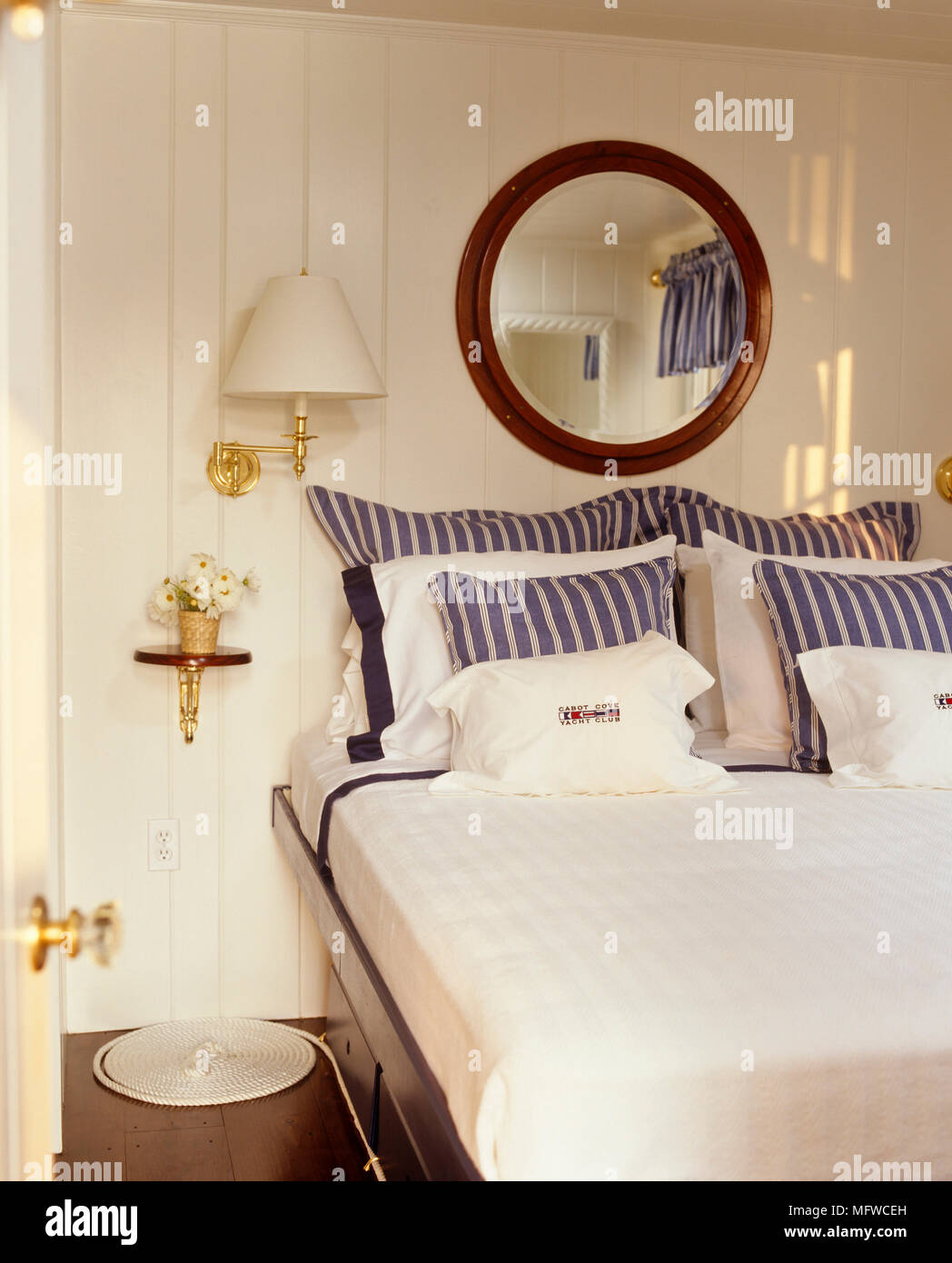 Round mirror above double bed with blue and white stripe bedlinen - Stock Image