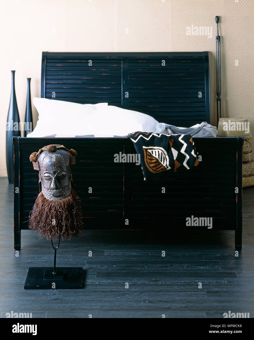 African Tribal Figure At End Of Black Painted Wooden Bed With Slatted Headboard Stock Photo Alamy