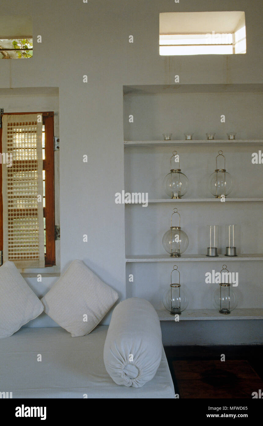 Collection of glass lanterns displayed on shelves behind sofa in ethnic style room - Stock Image
