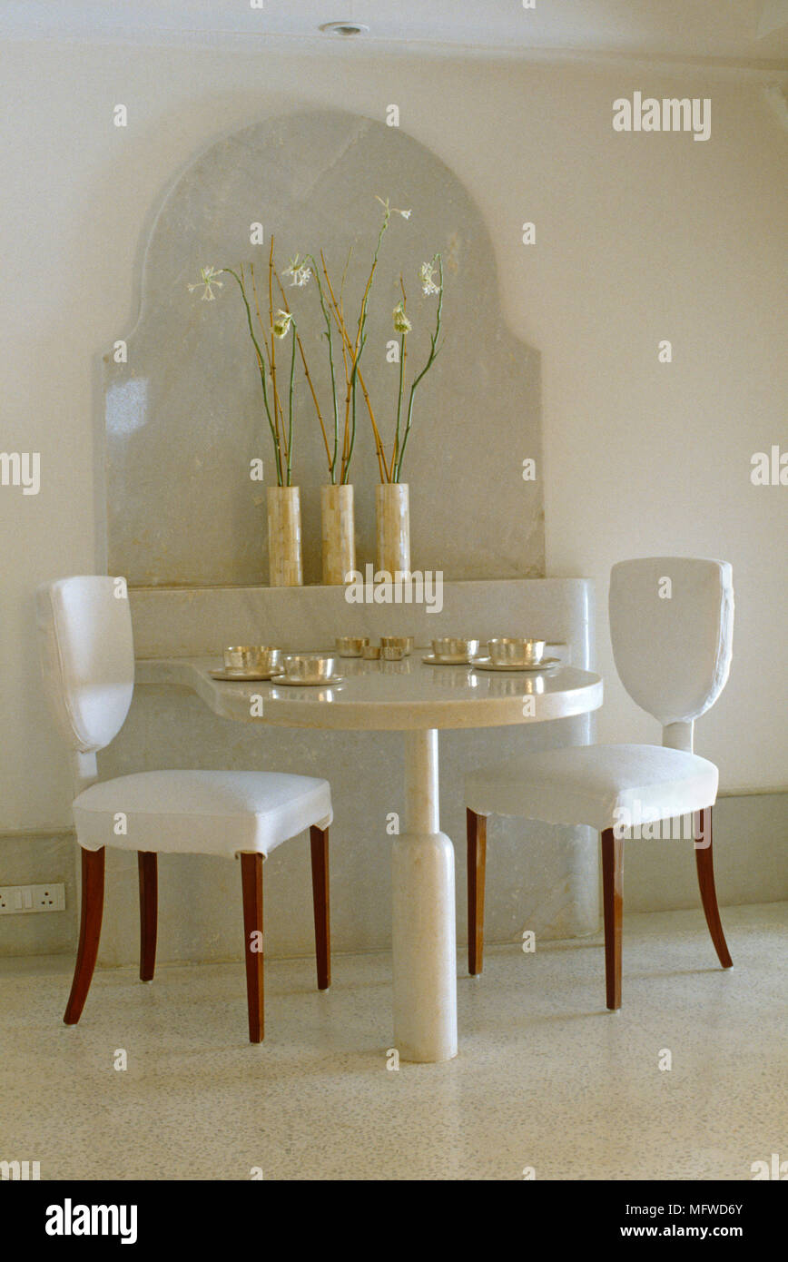 Pair Of Upholstered Chairs At Pedestal Table Set With Gold Tableware