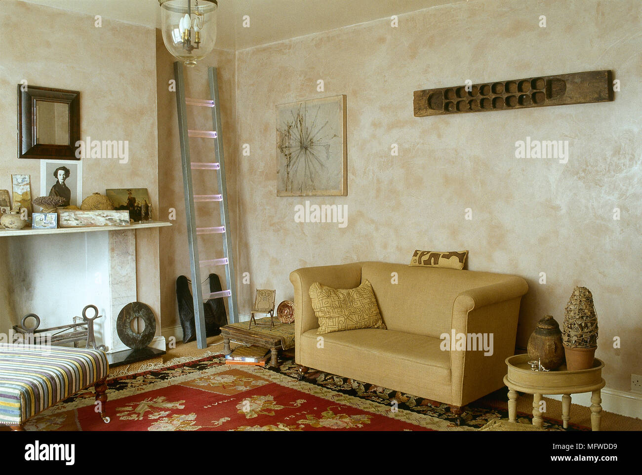 A country, sitting room in neutral colours, with sofa, upholstered ottoman, fireplace, - Stock Image