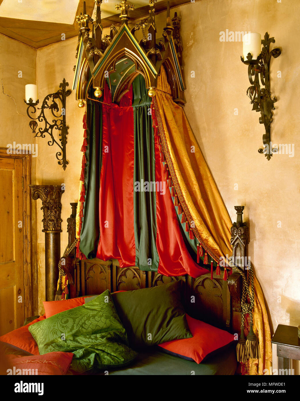 A Gothic Styled Bedroom With Yellow Walls Beamed Ceiling Gold Canopy Red Green Bed Linen Iron Candle Sconces Stock Photo Alamy