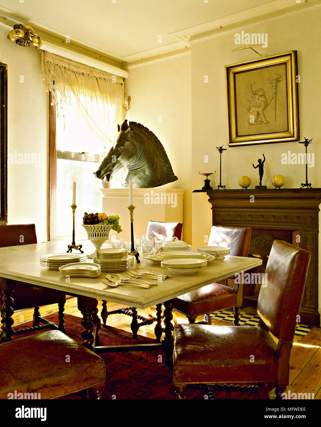 A traditional dining room with white walls, fireplace, tableware ...