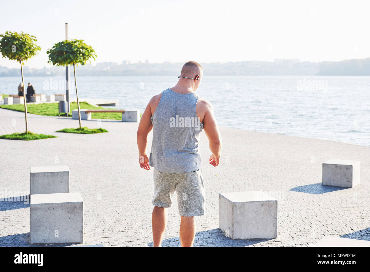 Young male jogger athlete training and doing workout outdoors in city - Stock Image