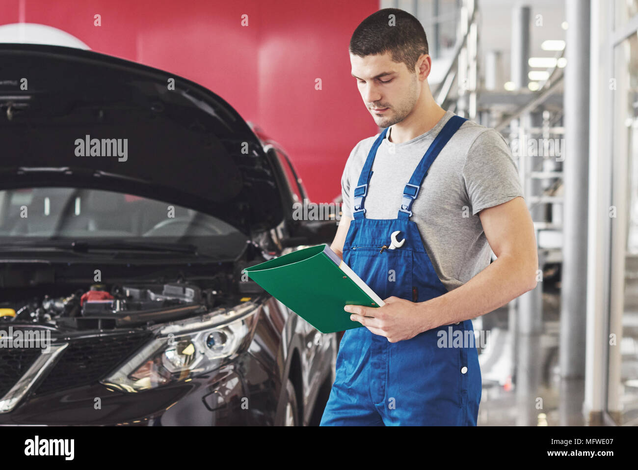 car service, repair, maintenance and people concept - auto mechanic man or smith with clipboard at workshop - Stock Image