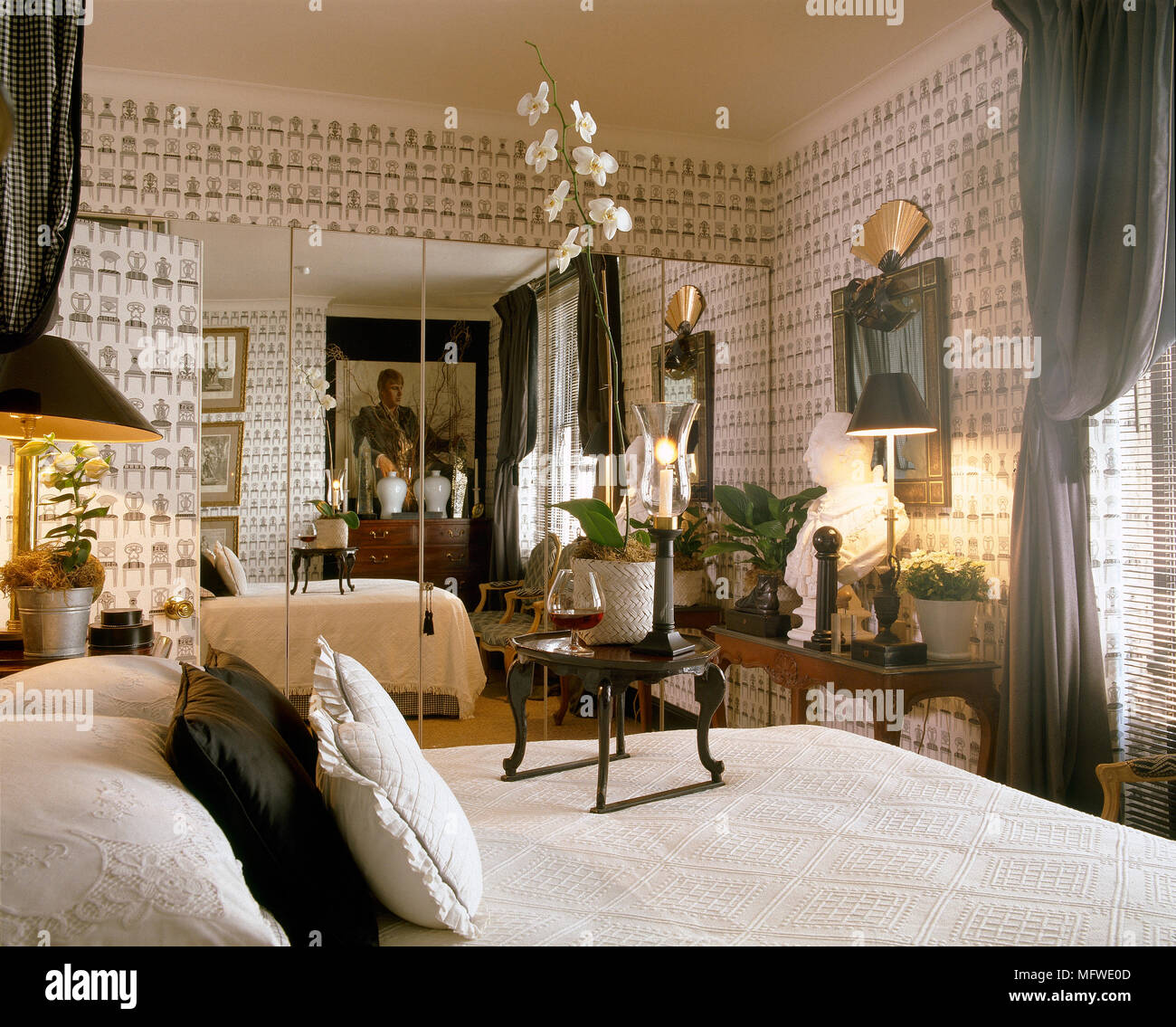 double bed in bedroom with pattern wallpaper and built in mirrored