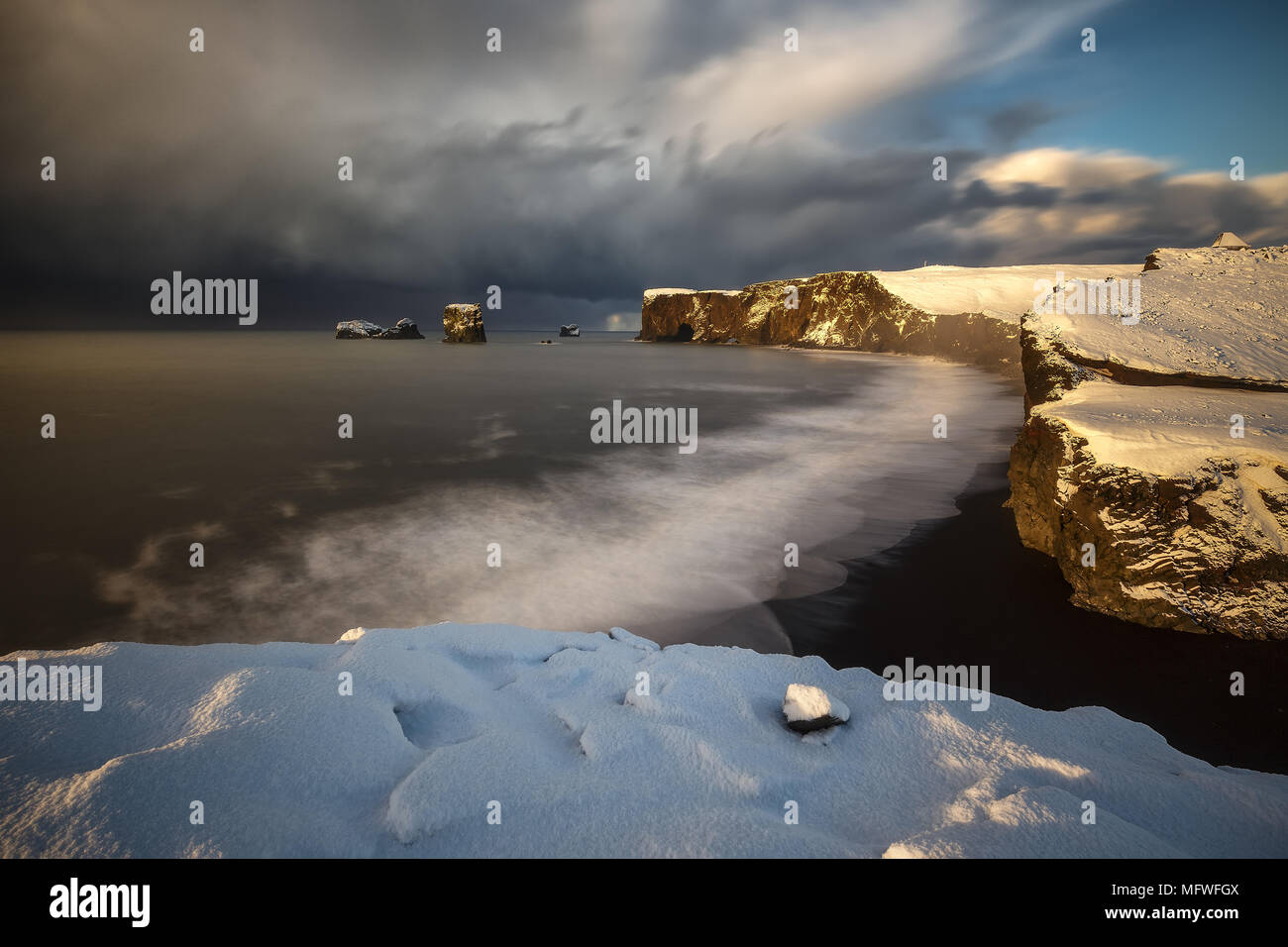 Dyrholaey cape over black sand beach in Iceland - Stock Image