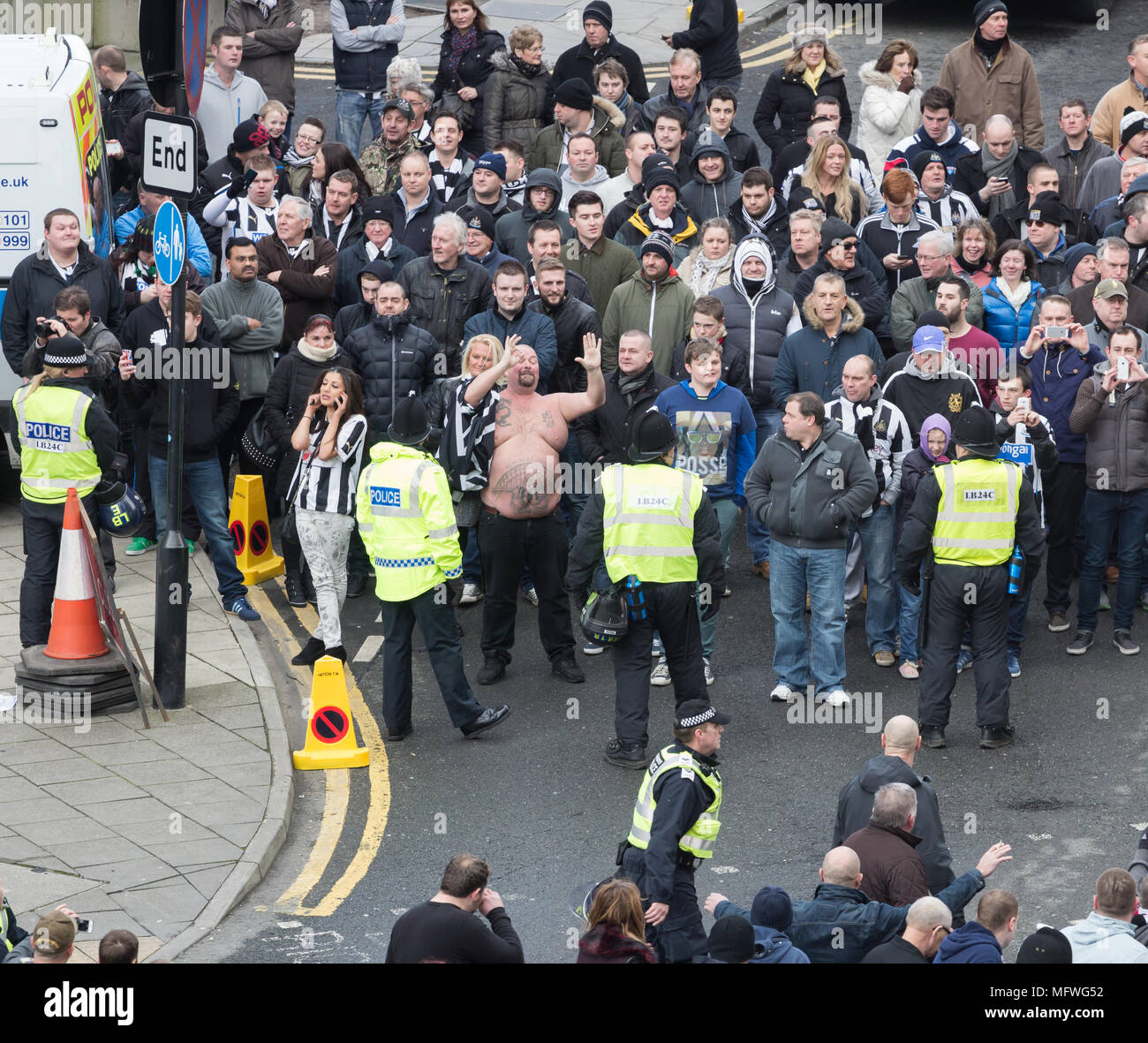 Newcastle United supporters taunting Sunderland supporters who are being escorted to stadium from train station Newcastle v Sunderland match. UK - Stock Image