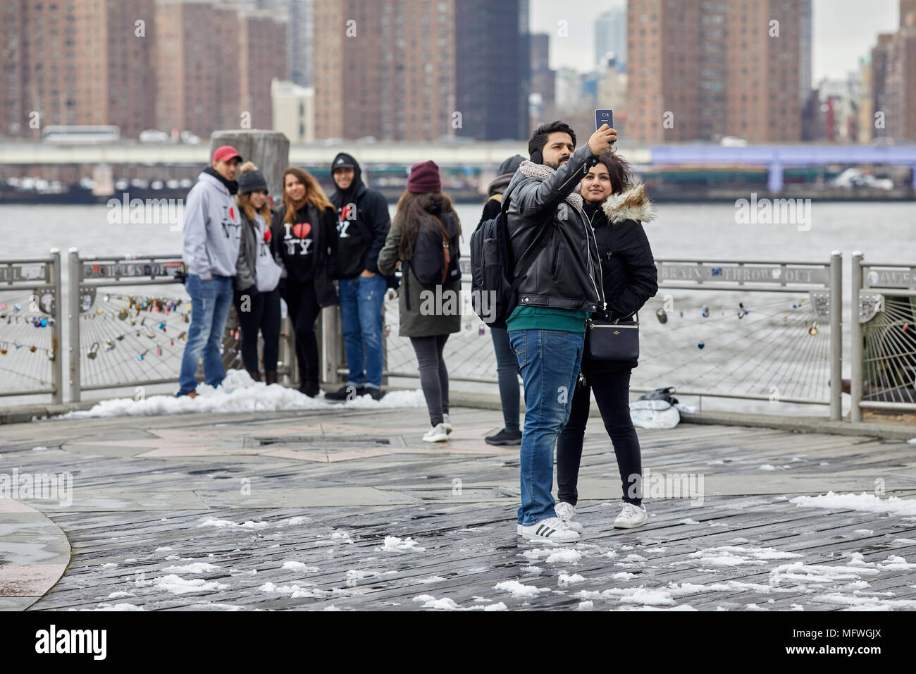 Brooklyn in New York City, tourists take pictures with landmark view of skyline - Stock Image