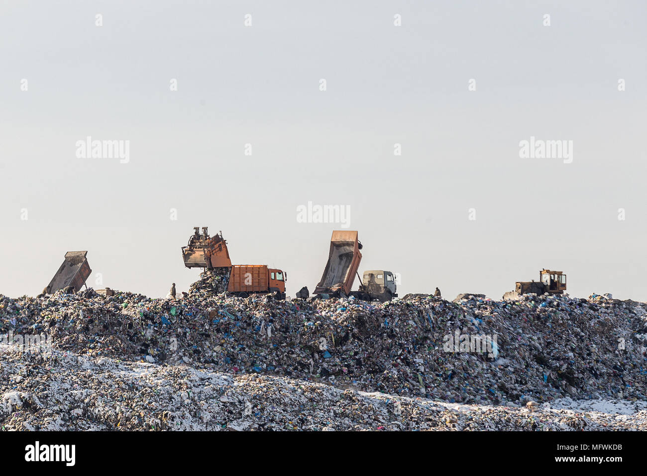 Dump trucks unloading garbage over vast landfill.  Environmental pollution. Outdated method of wasate disposal. Survival of times past - Stock Image