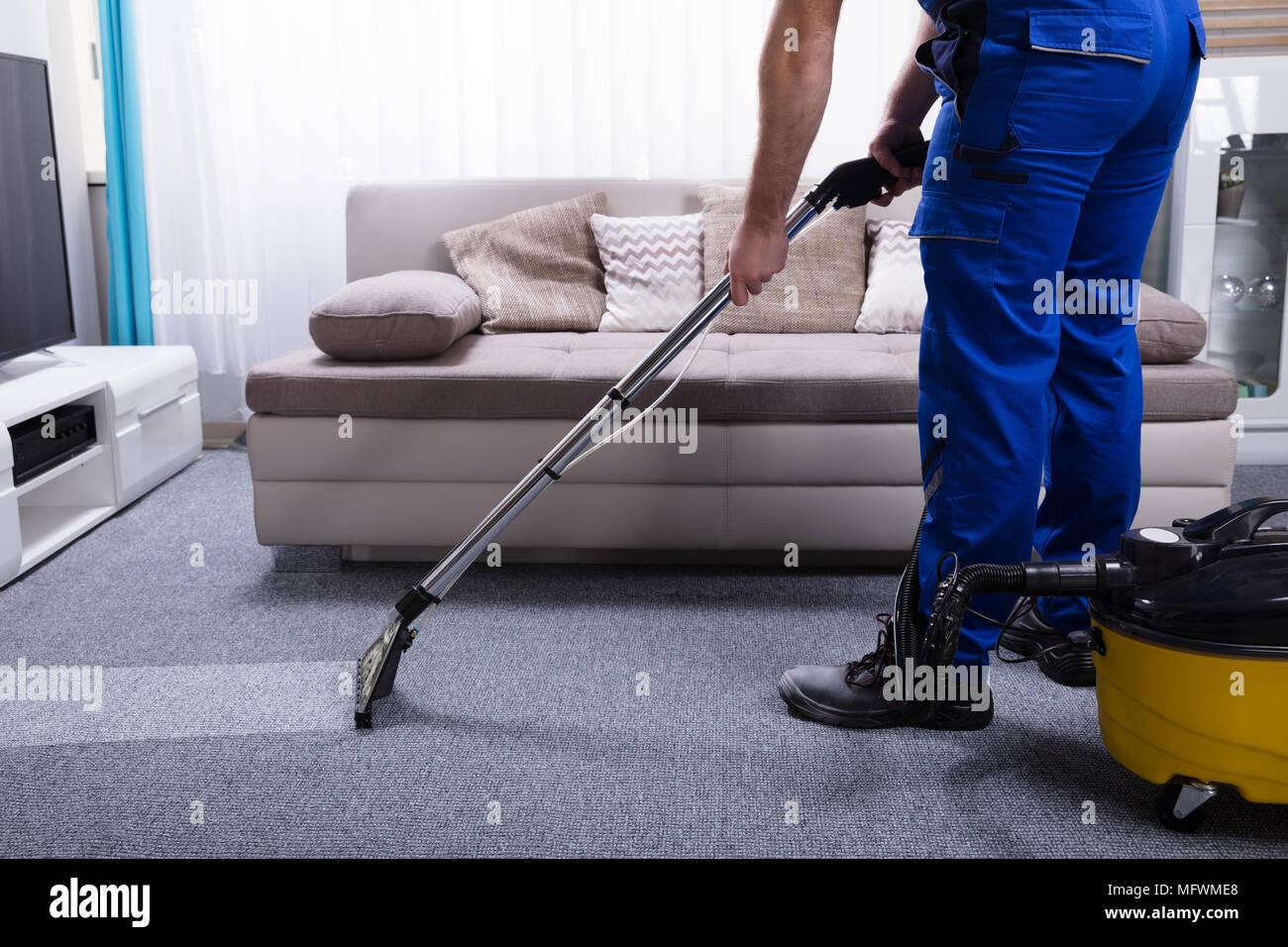 Janitor's Hand Cleaning Carpet With Vacuum Cleaner - Stock Image