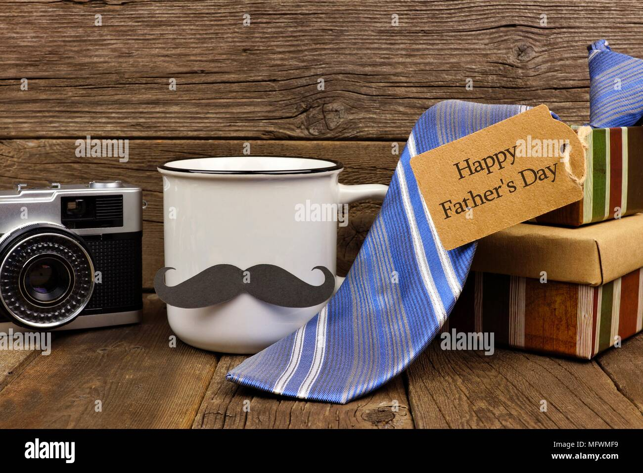 Group of Fathers Day gifts with greeting card. Side view on a rustic wood background. - Stock Image