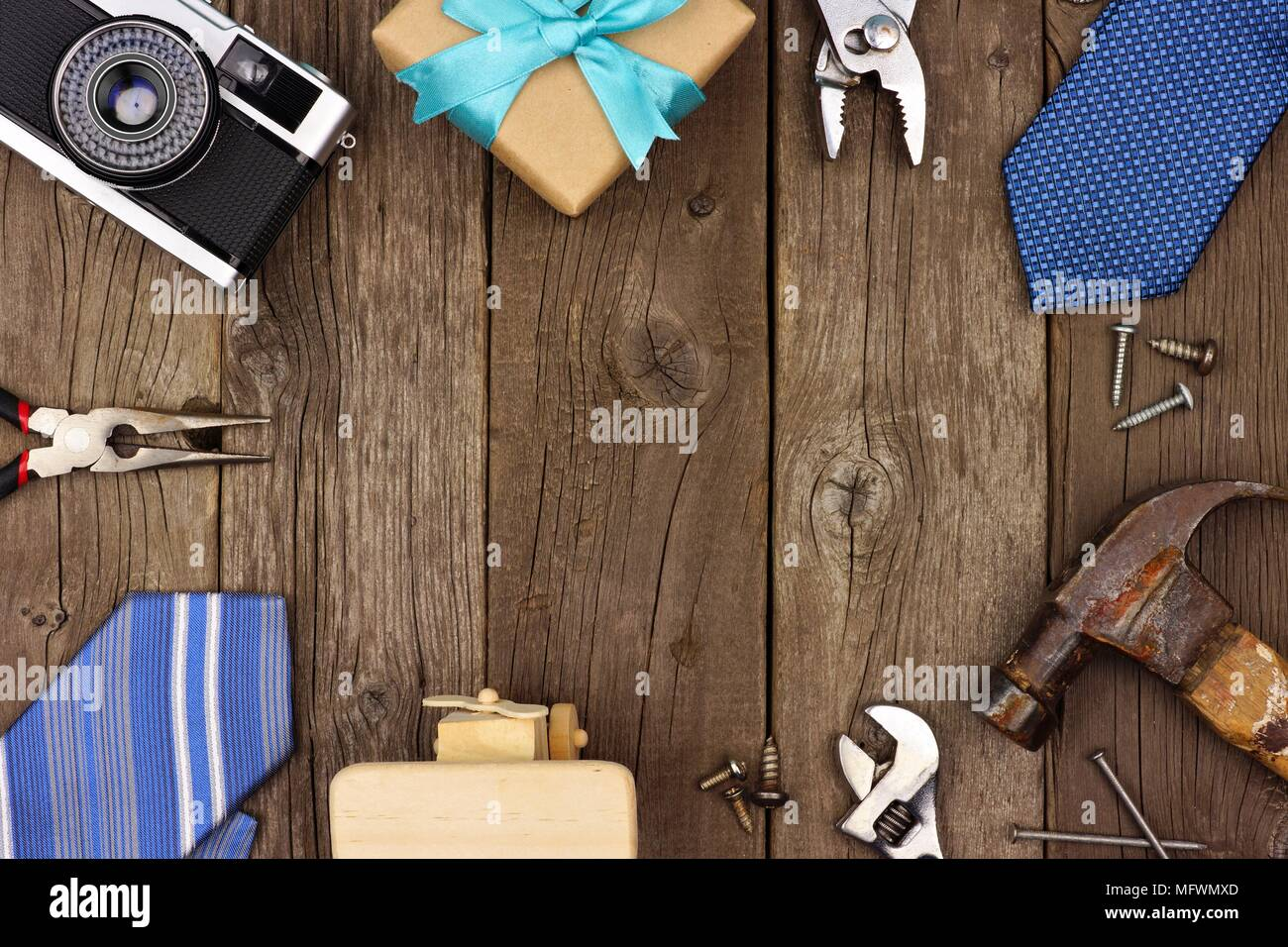Fathers Day theme frame of gifts, ties and tools on a rustic wood background. Top view with copy space. Stock Photo