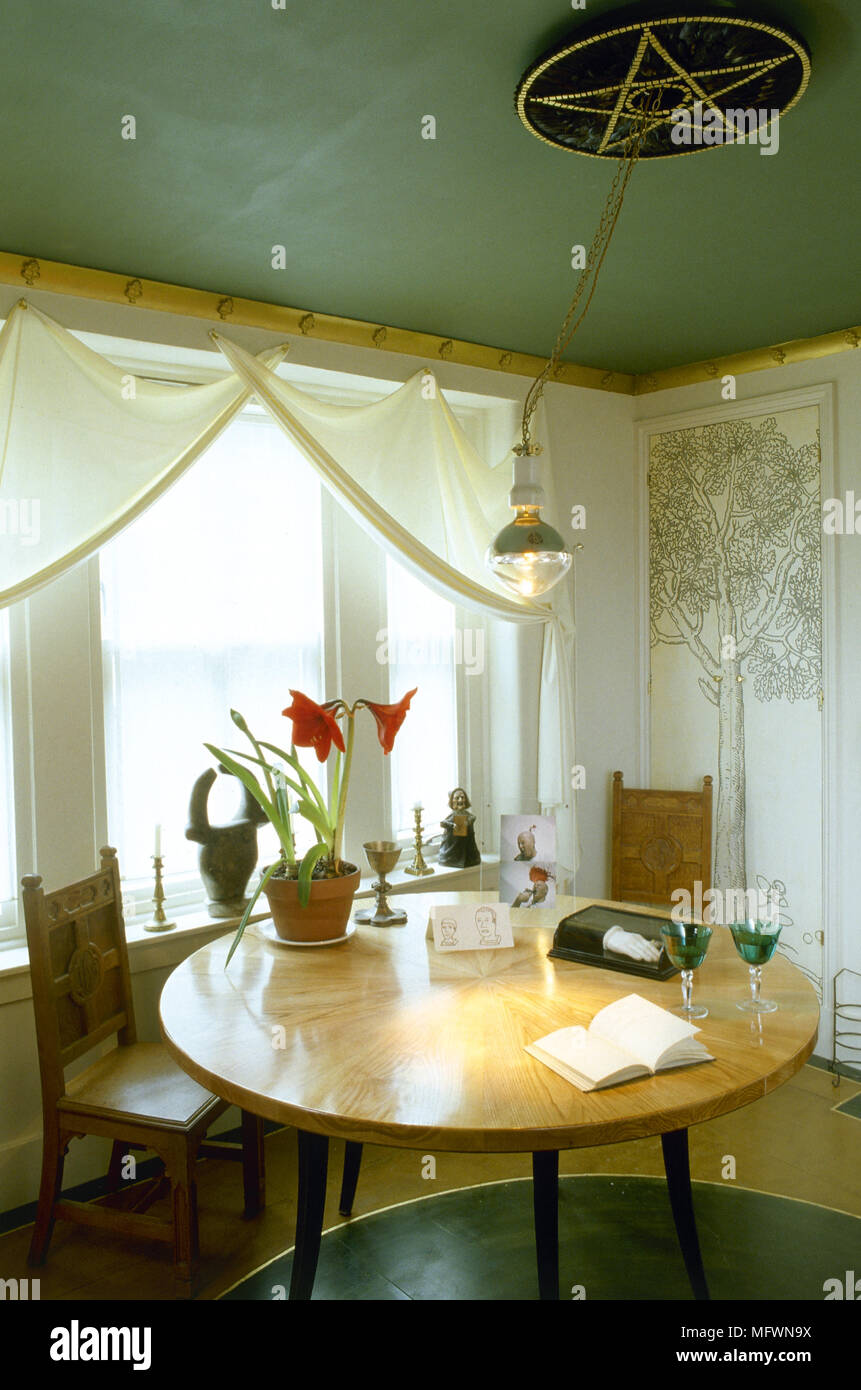 Modern Dining Room With Green Painted Ceiling, White Curtains Over A Sunny  Window, And A Round Wood Dining Table And Chairs.