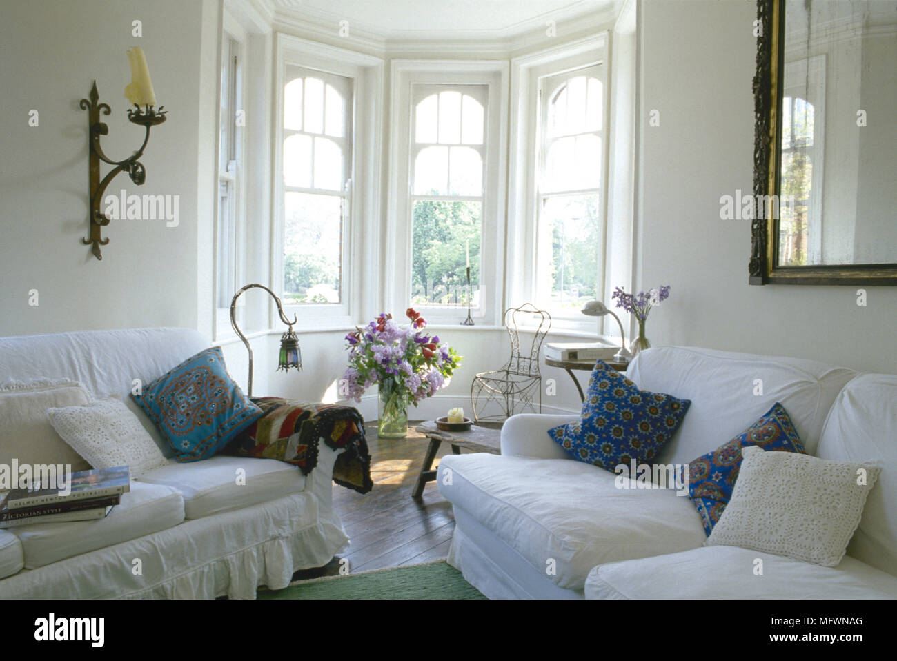 Traditional sitting room with overstuffed sofas and a sunny bay ...
