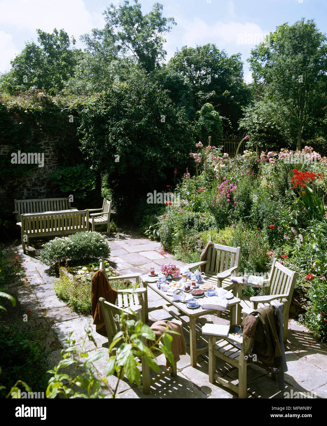 Back patio with wooden outdoor dining table and chairs bench seating area and blooming garden