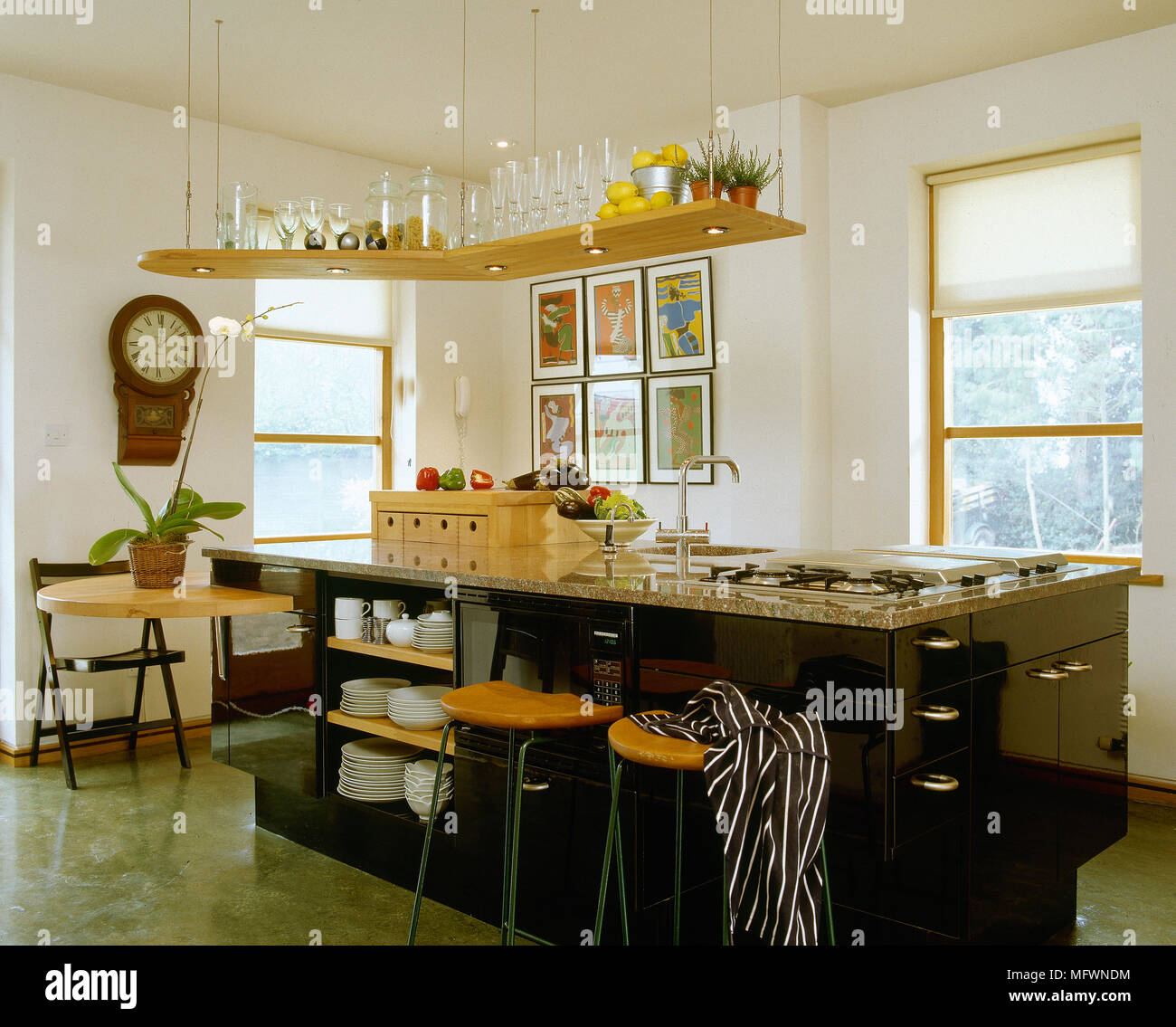 Modern kitchen with a central island breakfast bar, tile floor, and a suspended shelf with recessed lighting. - Stock Image