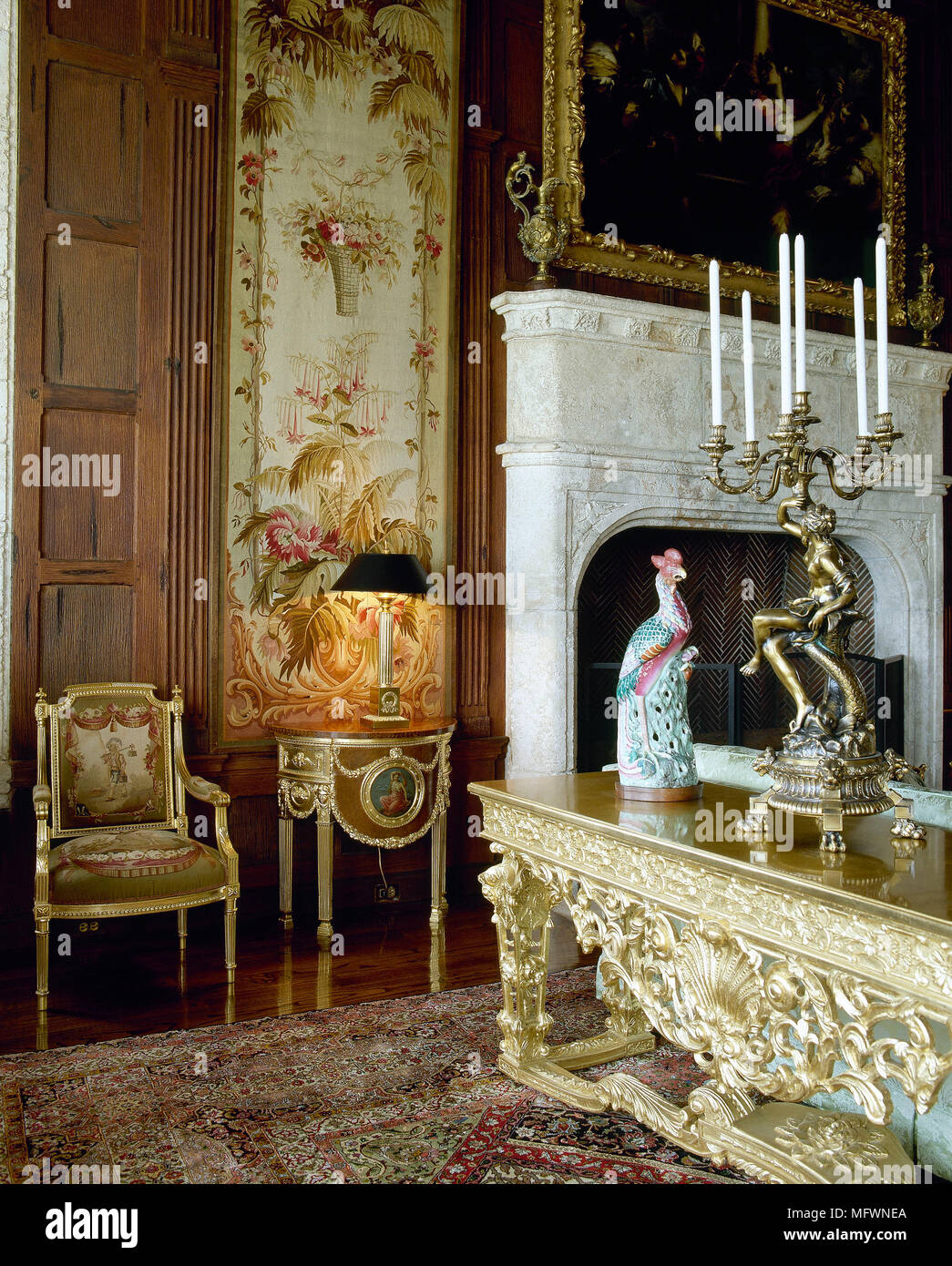 Traditional Drawing Room With Wood Panelling, Marble Fireplace, Gilded  Furniture, And An Oriental Rug And Tapestry.