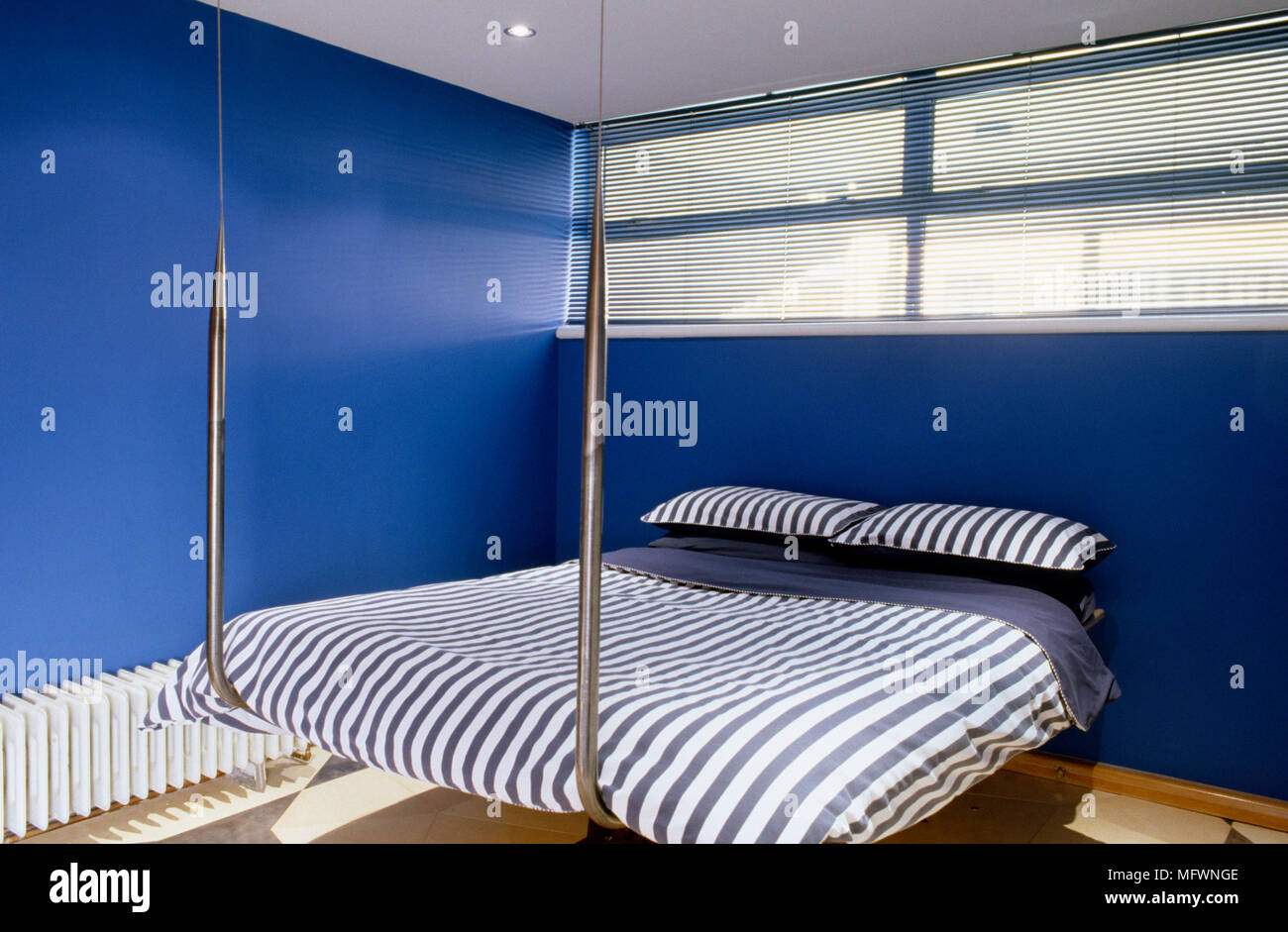 Suspended metal bed with striped bed linen beneath high ...