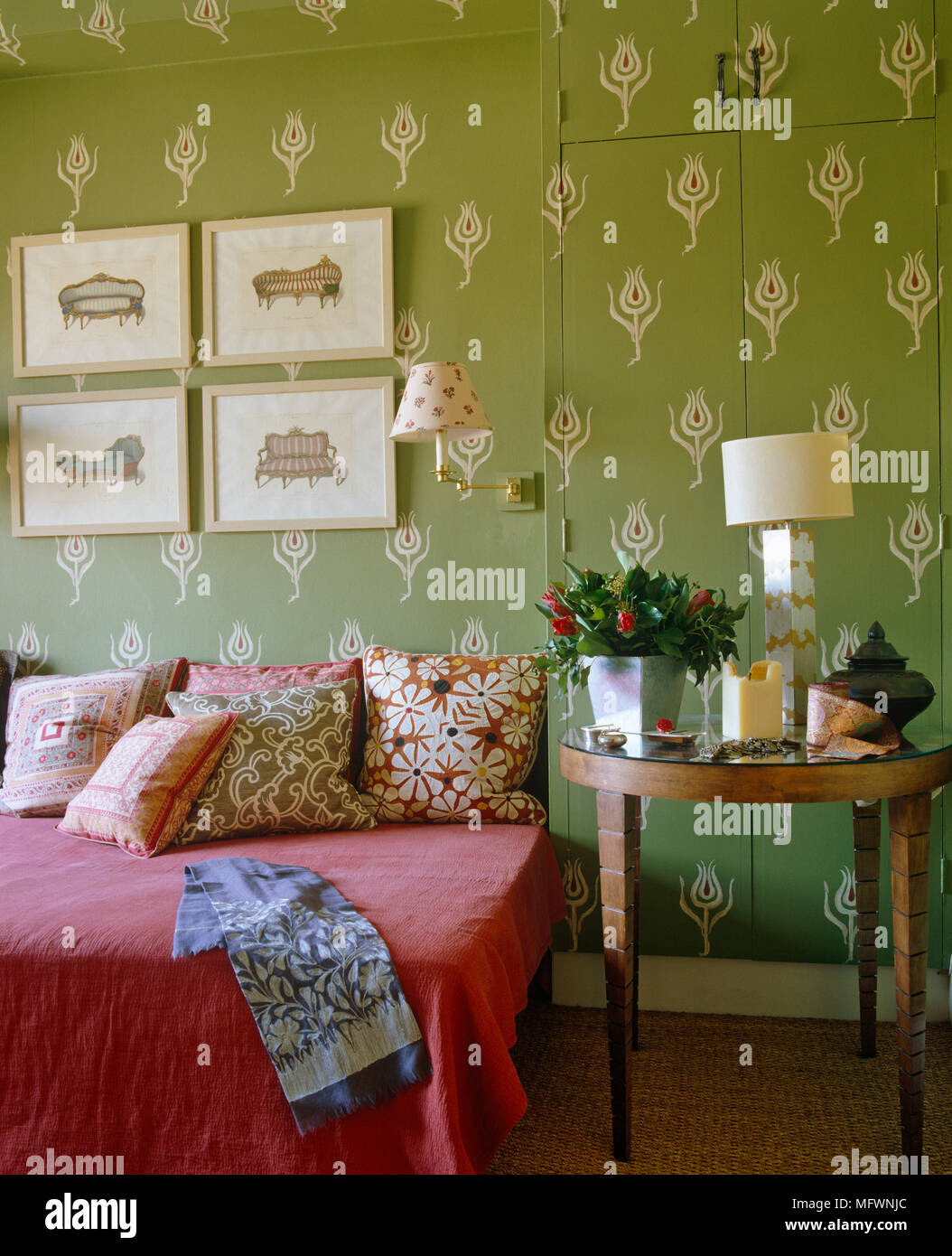 lamp on wooden table next to double bed with red cover and cushions rh alamy com