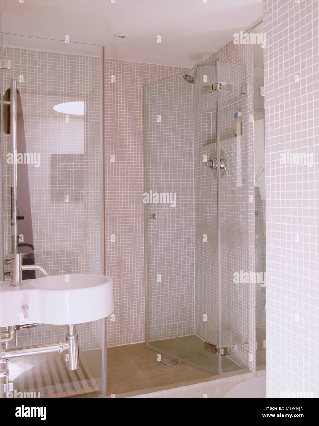 A detail of a modern, neutral bathroom with mosaic tiled walls, a ...