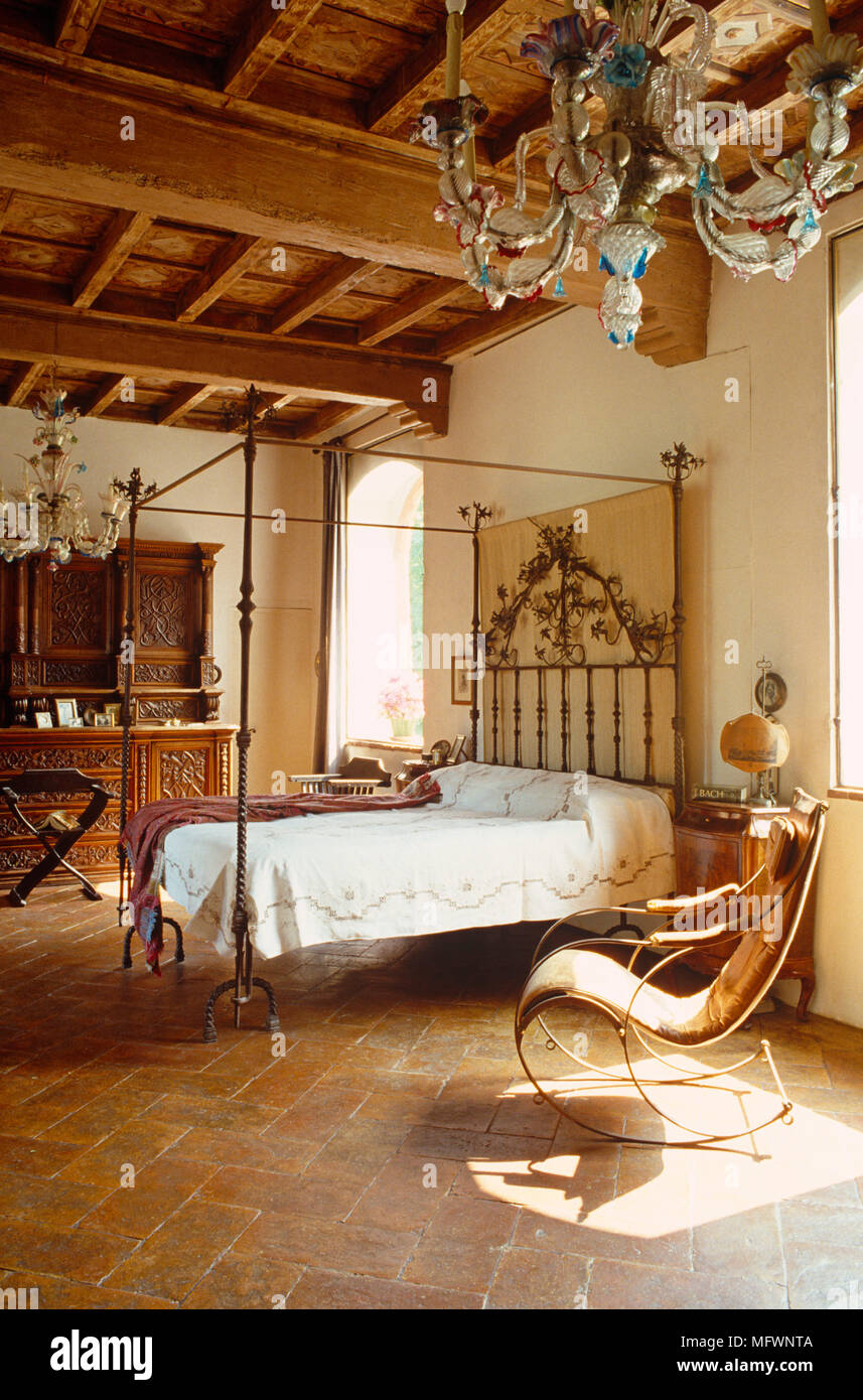 Antique wrought iron four poster bed in rustic bedroom for Arredamento rustico italiano