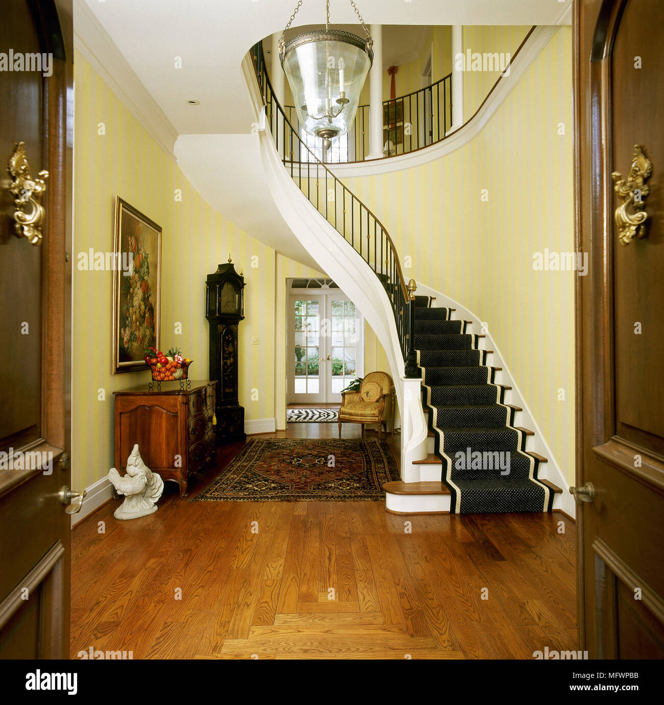 yellow hallway and front door entrance with curving staircase and
