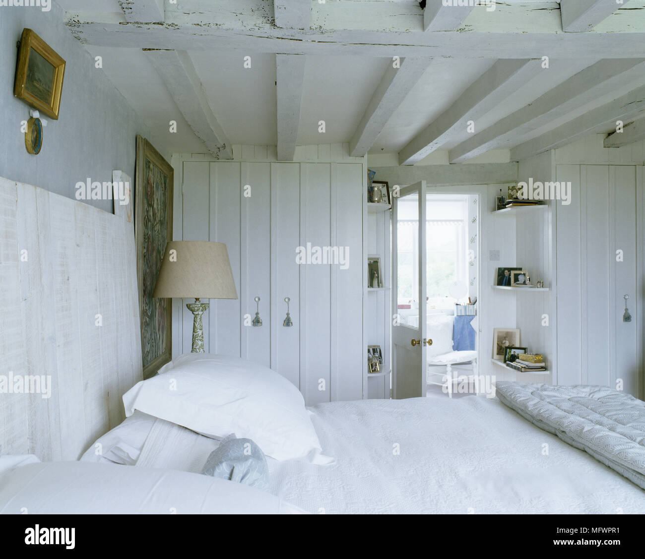Rustic Bedroom With Double Bed With White Linen And Wooden Headboard Next To Artwork And Lamp Stock Photo Alamy