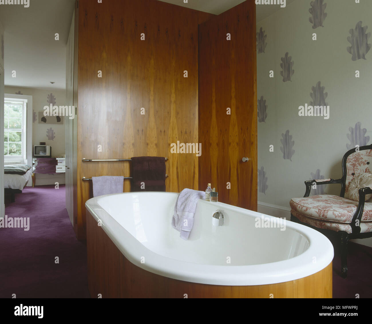 Wood panelled bathtub next to upholstered chair and wooden panelled ...