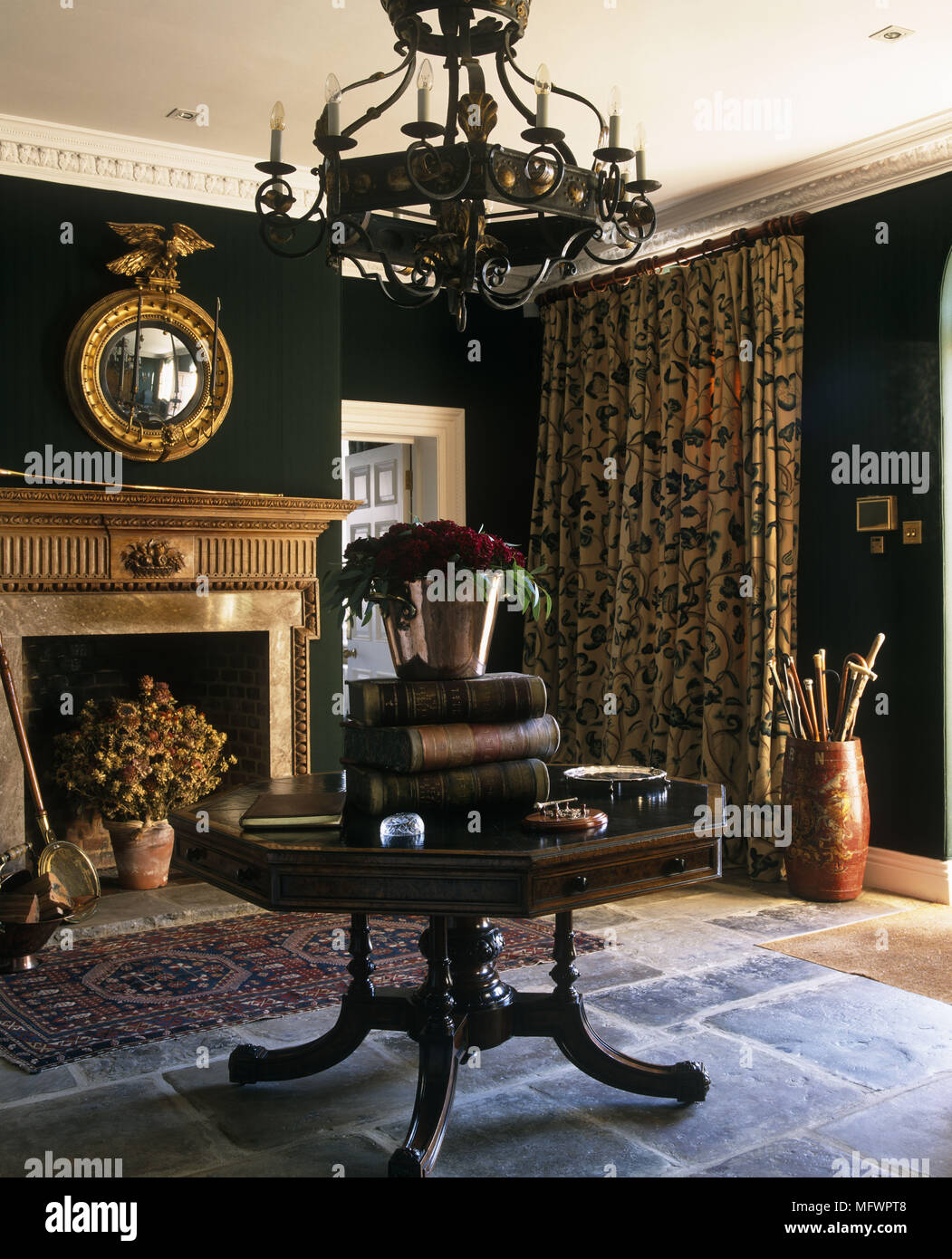 Traditional dining room with chandelier suspended over octagonal traditional dining room with chandelier suspended over octagonal table on flagstone floor next to fireplace with rug and flowers aloadofball Gallery