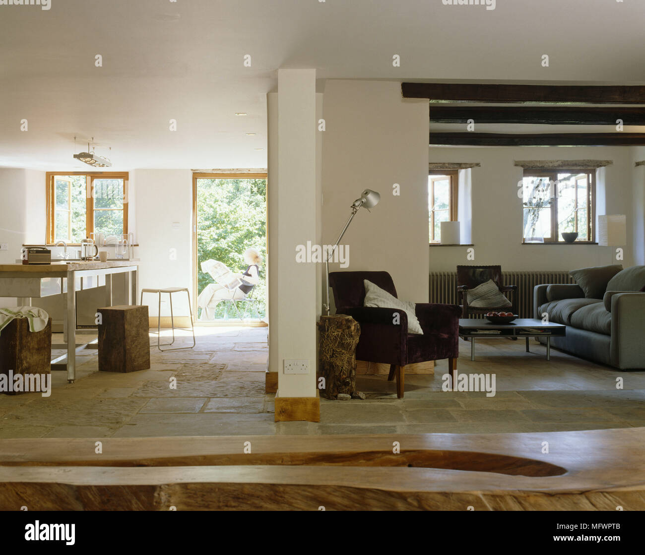 Wooden Bench In Front Of Sitting Room Area With Exposed Beams And Next To Dining Flagstone Floor