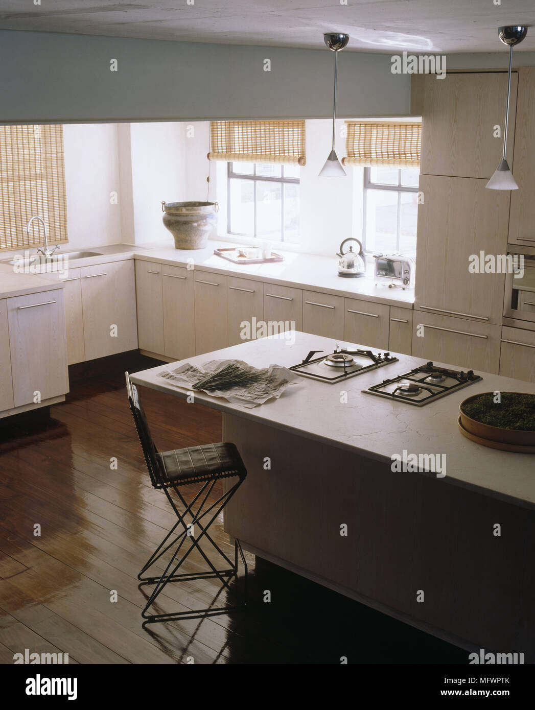 Kitchen With Metal Stool At Breakfast Bar Unit With Hob And On