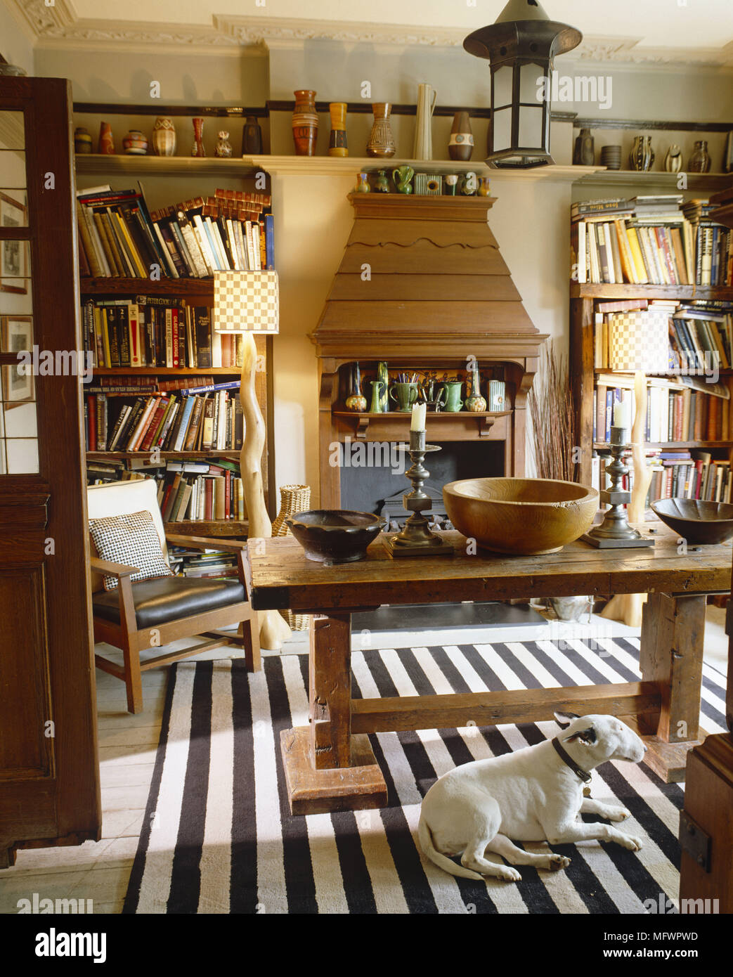 Dog Lying On Striped Rug Next To Rustic Wooden Dining Table And Fireplace In Between Two Bookshelf Units