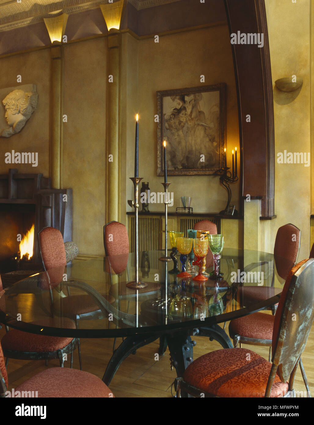 Glass Topped Dining Table With Upholstered Red Chairs Next To Open Fireplace Stock Photo Alamy