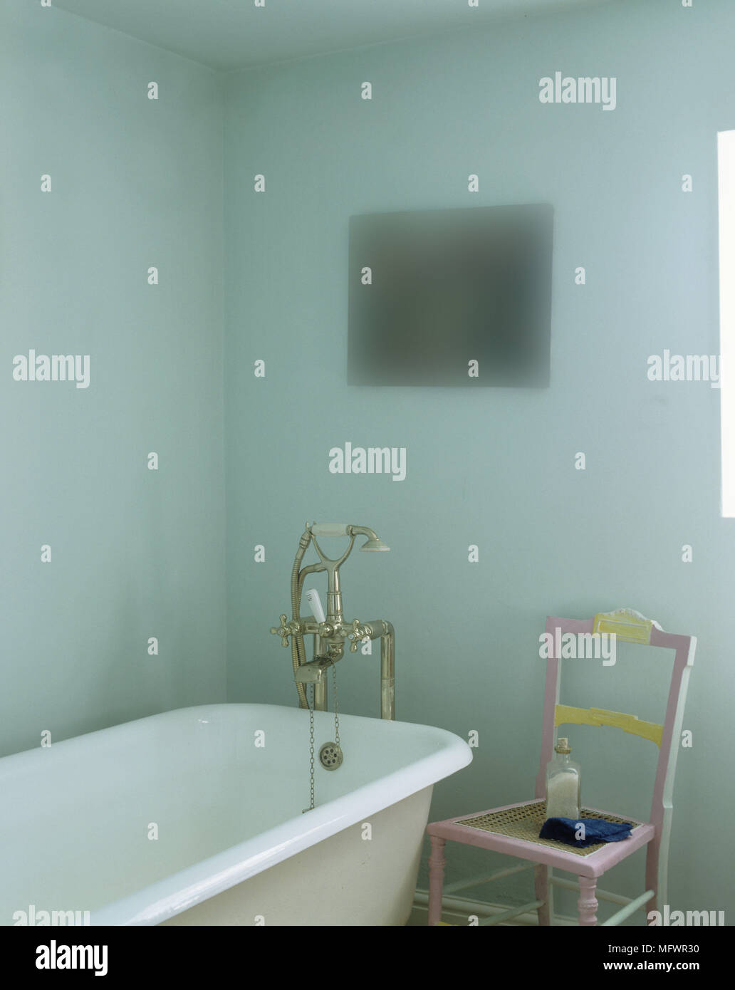 Pink painted chair next to freestanding bathtub in blue bathroom ...