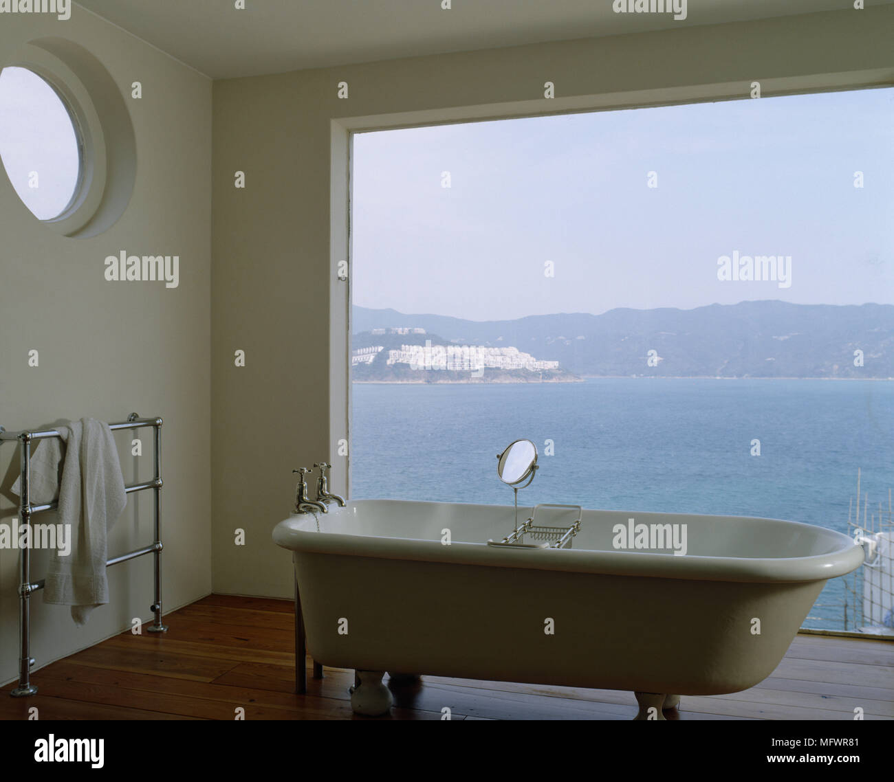 Freestanding bath in front of large window with sea view Stock Photo ...