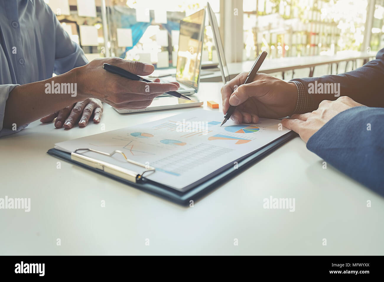 Business concept. Business people discussing the charts and graphs showing the results of their successful teamwork. - Stock Image