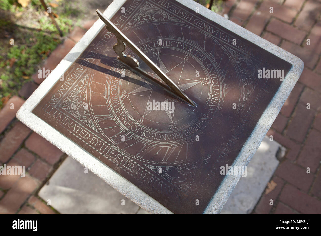Still life of an antique handmade bronze sundial seen in the courtyard in colonial Williamsburg Virginia - Stock Image
