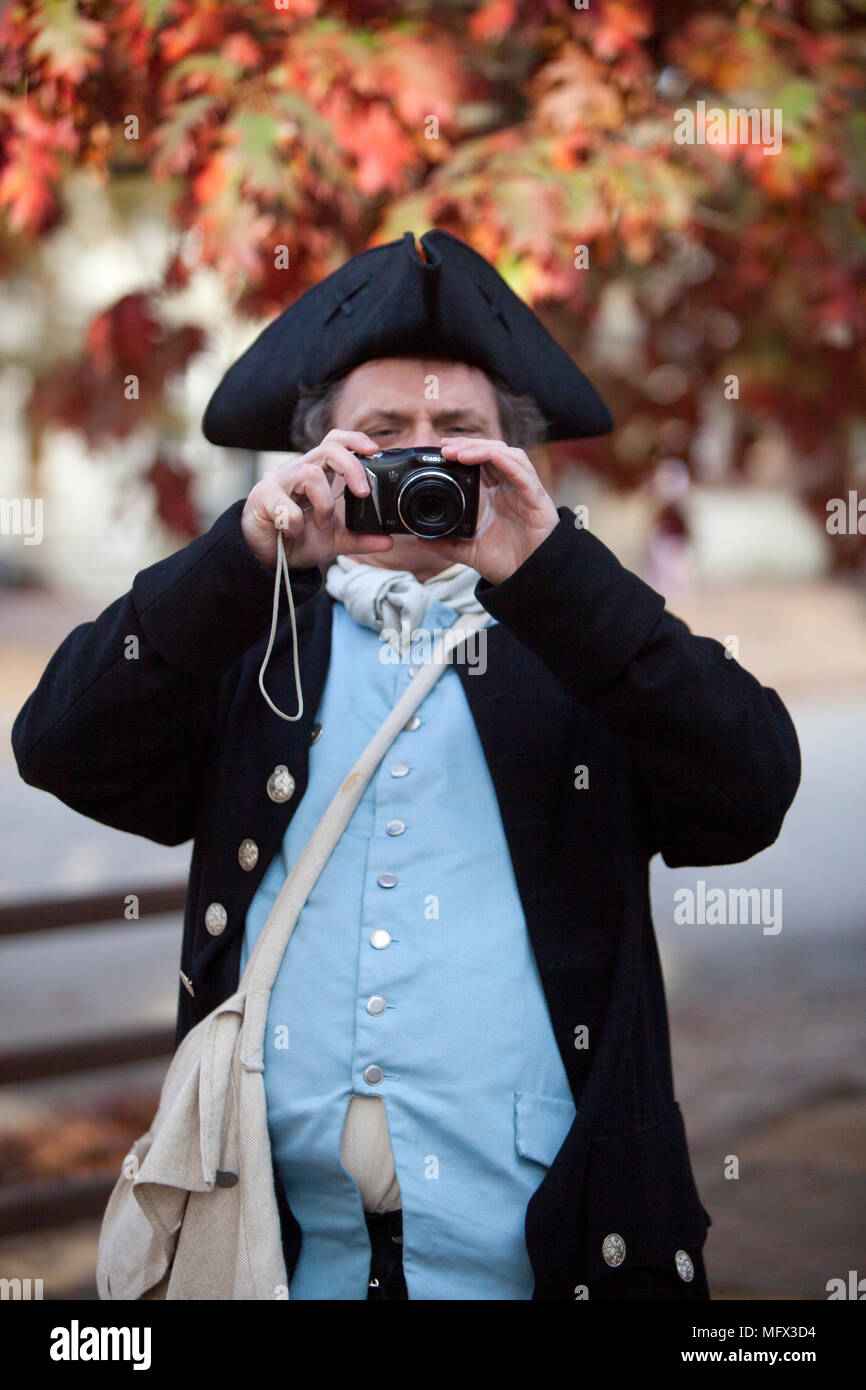 An amusing photo of an actor in  18 century costume using a 21st-century digital camera in colonial Williamsburg Virginia Stock Photo