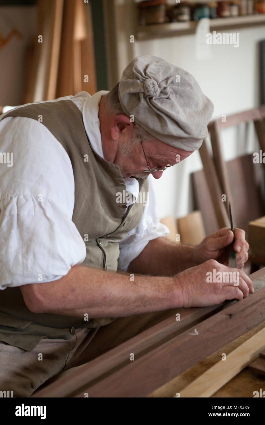 Cabinet maker in authentic early American clothing working in his shop surrounded by his authentic tools in colonial Williamsburg Virginia - Stock Image