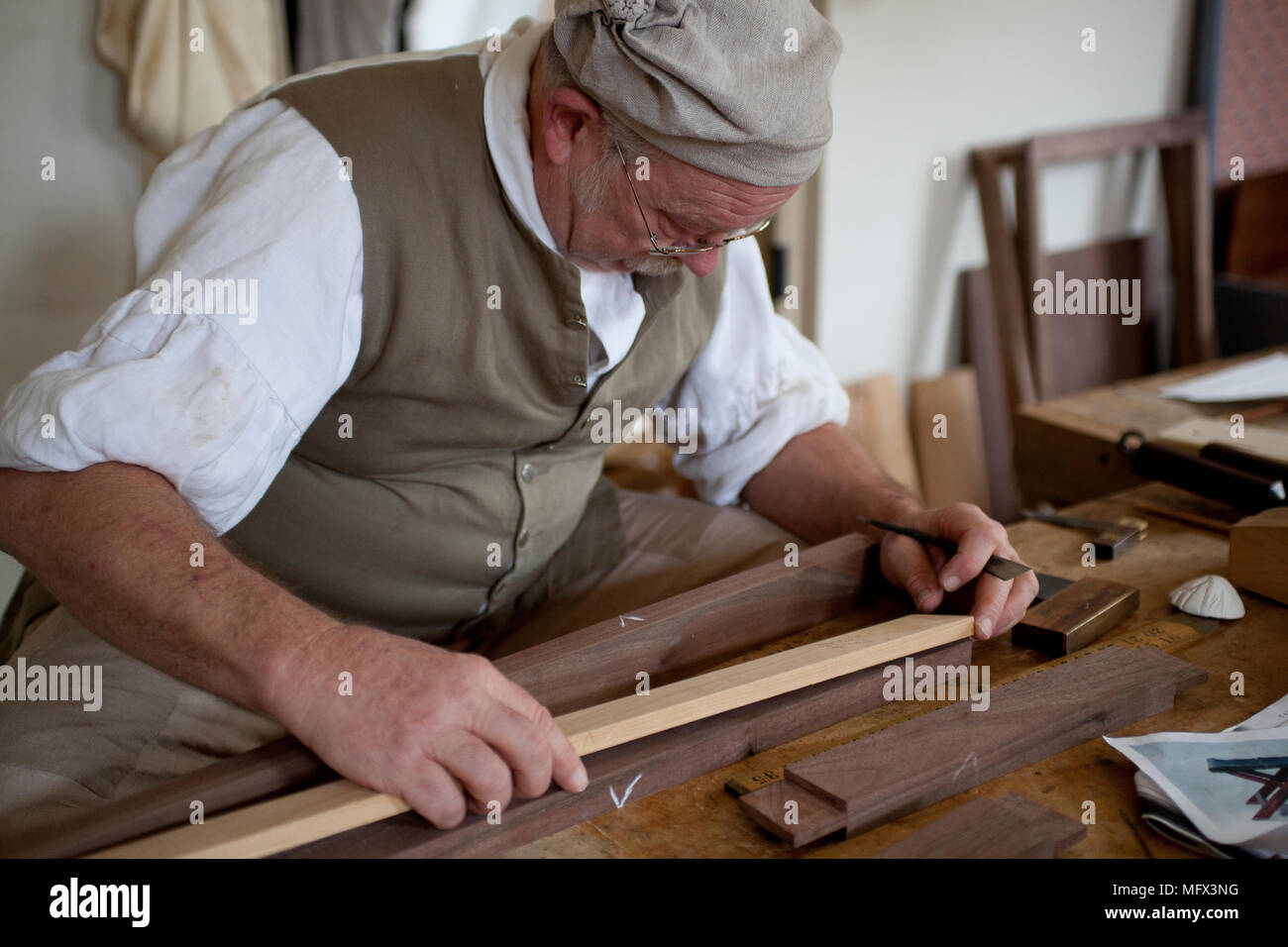 Cabinet maker in authentic early American clothing working in his shop surrounded by his authentic tools in colonial Williamsburg Virginia Stock Photo